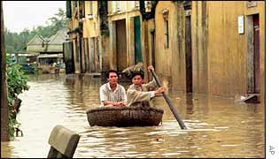 Vietnamese men paddle their way down a street in a basket in Hoi An in Quang Nam province in central Vietnam, 1999