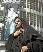 Iraqi woman by poster of Saddam in Baghdad