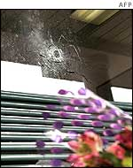 Flowers on a bench under a bullet hole, at the scene of one killing in Aspen Hill, Maryland
