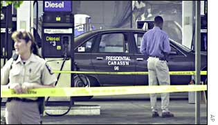 Police officer inspects a taxi where a man was shot dead at a petrol station