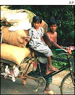 Family transporting belongings by tricycle in Bangladesh