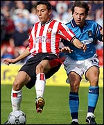 Fabrice Fernandes shields the ball from Eyal Berkovic