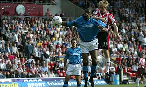 Brett Ormerod rises above Sylvain Distin to score his first goal against Manchester City