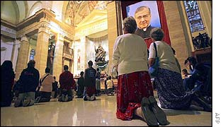 Pilgrims pray in front of the remains of Opus Dei founder Jose Maria Escriva de Balaguer in Rome