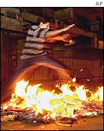 A boy jumps over a fire started during a protest in Ramallah