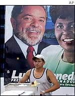 Man walking past a Lula election poster