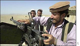 Militiamen loyal to an Afghan warlord prepare their guns