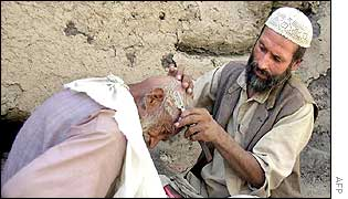 An Afghan barber shaves a man's head