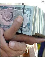 Someone holding a large amount of Afghan currency