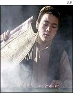 A youth cooks at a street barbeque in Kabul