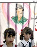 Iraqi girls sit under a drawing of President Saddam Hussein