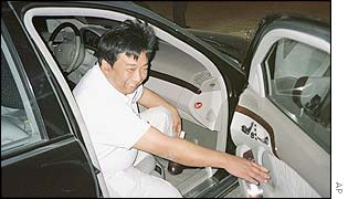 Chinese businessman Yang Bin gets into his car after a dinner at his Holland Village development in Shenyang, China, Monday Sept. 30, 2002.