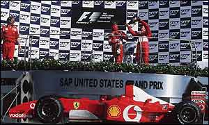 Michael Schumacher and Rubens Barrichello celebrate on the podium of the US Grand Prix