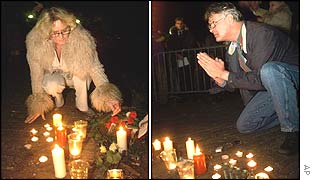 Two people light candles and pray in front of the royal palace