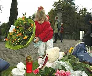 A little girl lays flowers for Prince Claus