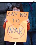 A girl holds an anti-war sign