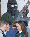 Schoolgirls play in front of an IRA Mural in Belfast
