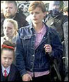 Catholic parents escort their children with RUC Officers in riot gear to the Holy Cross School in Belfast