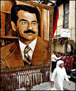 Man walks under portrait of Saddam Hussein