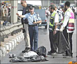 Policewoman and volunteers stand near the remains of the suicide bomber