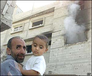 Palestinian residents stand by a burning building after it was hit by a tank shell