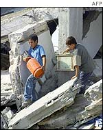 Palestinian children salvage some personal effects found in the rubble of their house which was demolished by Israeli army bulldozers 10 October 2002 in the southern Gaza Strip refugee camp of Rafah