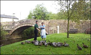 Store owner Phil Woodhead and employee Jean Sutcliffe feed the ducks at Dunsop Bridge