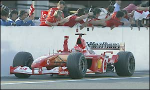 Michael Schumacher salutes the crowd after victory