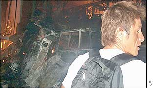 A foreign tourist looks on as a nearby disco burns