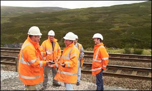 The centre of Scotland is on the hillside 250 metres behind these workers