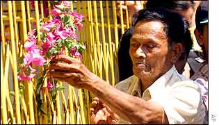 A Balinese man offers flowers near the bomb site, Kuta, Bali, Indonesia