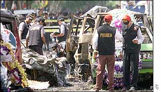 Indonesian policemen walk past flower displays placed at the site of the explosion in Kuta