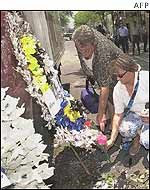 Tourists lay bouquets of flowers at the blast site in Legian street in the tourist area in Kuta