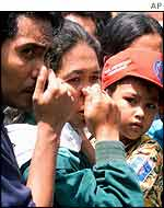 Onlookers outside Bali hospital hold their noses due to the smell