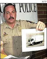 A police officer hands out pictures of a truck being sought