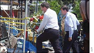 Australian Foreign Minister Alexander Downer (L) offers flowers with Australian Justice Minister Chris Ellison (R)