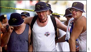 Australian tourists weep as they leave the site of a bomb blast which killed friends and relatives after laying wreaths at the site 15 Oct 2002