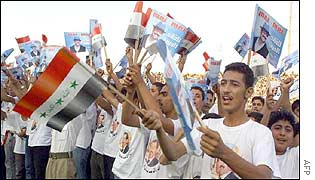 Iraqi youths wear t-shirts with President Saddam Hussein�s portrait and wave flags and portraits
