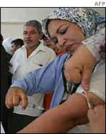 Iraqi woman takes blood from her arm to mark yes on her voting slip