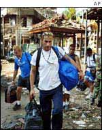 Tourists walk with their bags past the scene of the blast