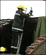 Fireman fixes a roof