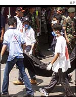 Rescue workers carrying a body bag from the bomb site