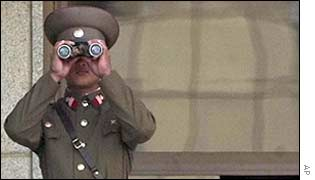 North Korean soldier looks through binoculars across the border with South Korea