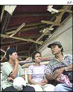Passengers sit outside a damaged bus station in Kidapawan, southern Philippines