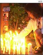 Candles are lit for victims of the bomb at a memorial service in Bali