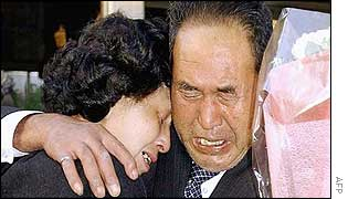Hitomi Soga (left) cries as she is hugged by her father Shigeru, on her arrival at her former home in Mano, northern Japan, 17 October 2002