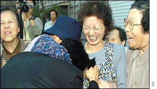 Kaoru Hasuike (foreground left) is embraced by his relatives