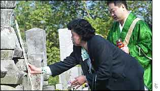 Japanese kidnapping victim Hitomi Soga adjusts her family tombstone as a Buddhist priest looks on, Sado Island, northern Japan,