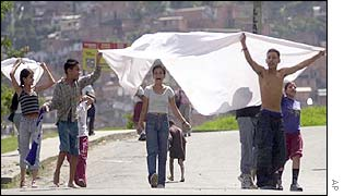 Residents carry a sheet to show they are peaceful in Medellin
