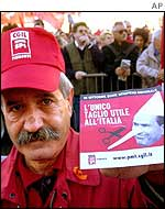 A striking worker carries a poster depicting Italian Premier Silvio Berlusconi as Pinocchio and reading